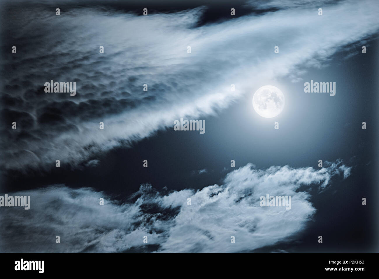 Full moon in the deep night sky amid the clouds above and below it - Stock Image