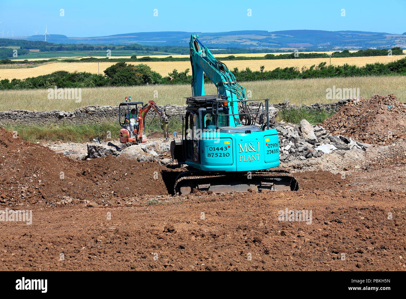Large versus small in the plant machinery world, two diggers at work in a field being restored to farmland after completion of building works. - Stock Image