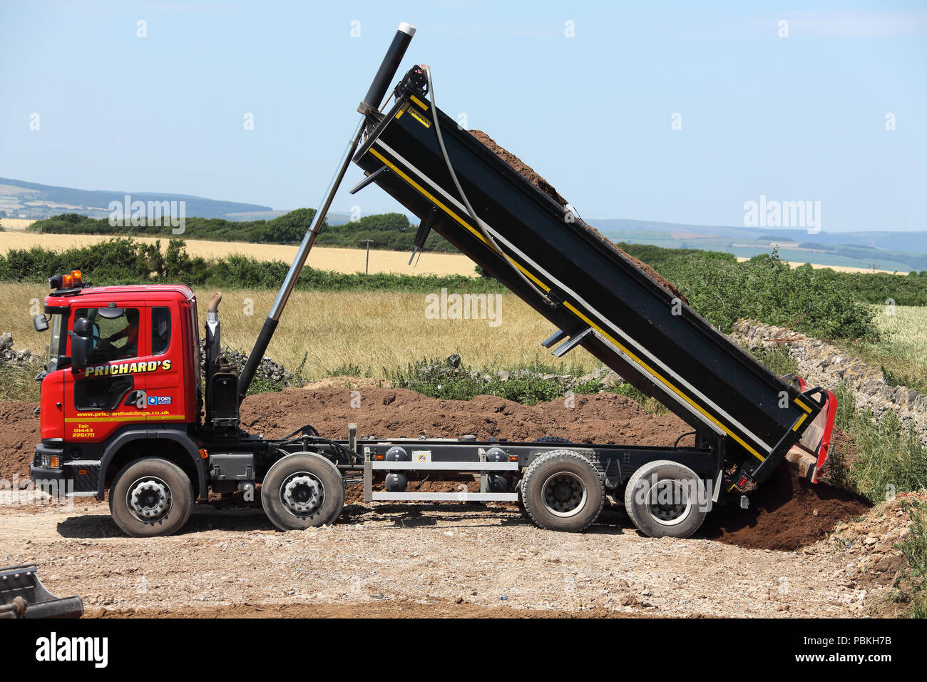 Anew tipper lorry delivering its full load of fresh earth during restoration of an ex building site with earth sliding out of the rear tailgate. Stock Photo