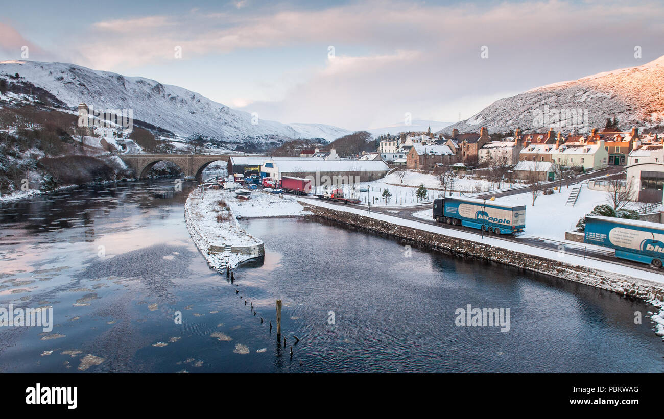 Snow lies on quaysides, cottages and mountainsides in the fishing village of Helmsdale on the Moray Firth coast of the Highlands of Scotland. - Stock Image