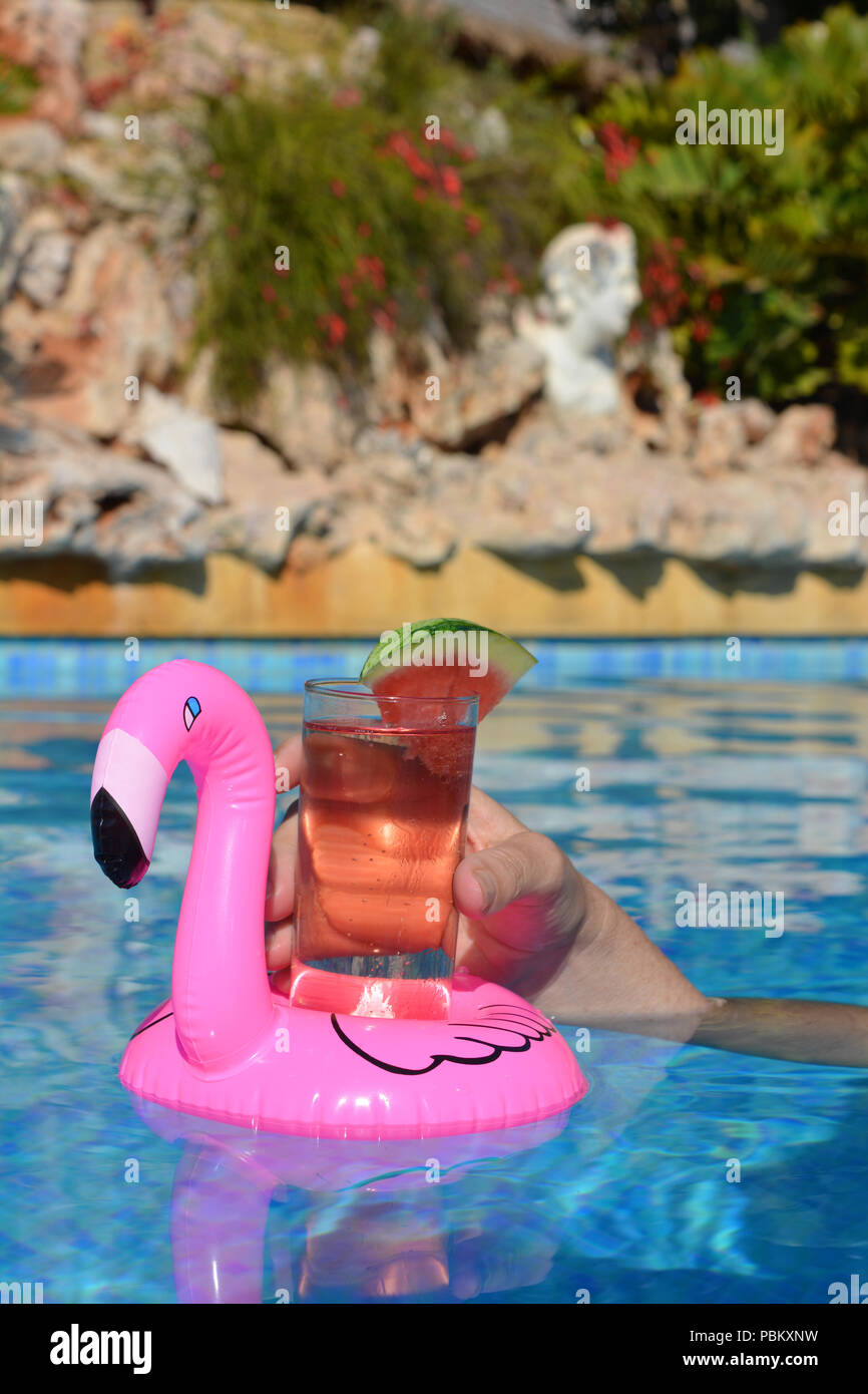 Womans Hand With A Cocktail In An Inflatable Pink Flamingo