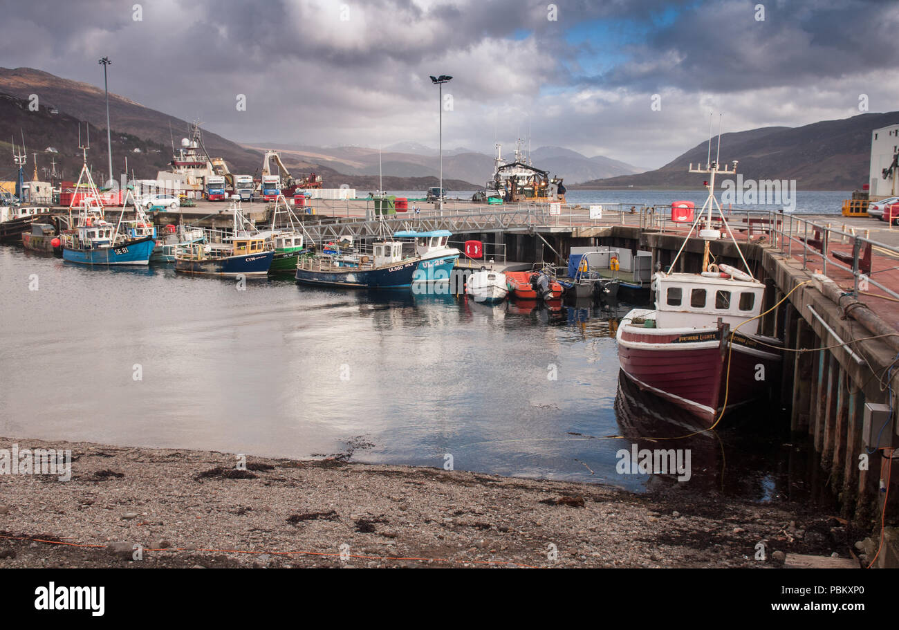 Ullapool, Scotland, UK - March 31, 2011: Fishing boats dock in the harbour alongside Ullapool Pier in Loch Broom, an inlet of the Atlantic on the west - Stock Image