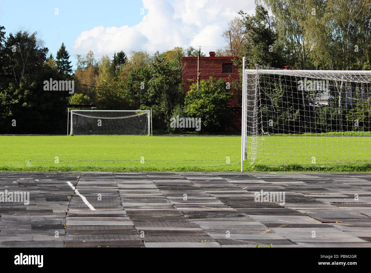 stadium: a treadmill with rubber plates and a football field with a goalkeeper's goals - Stock Image