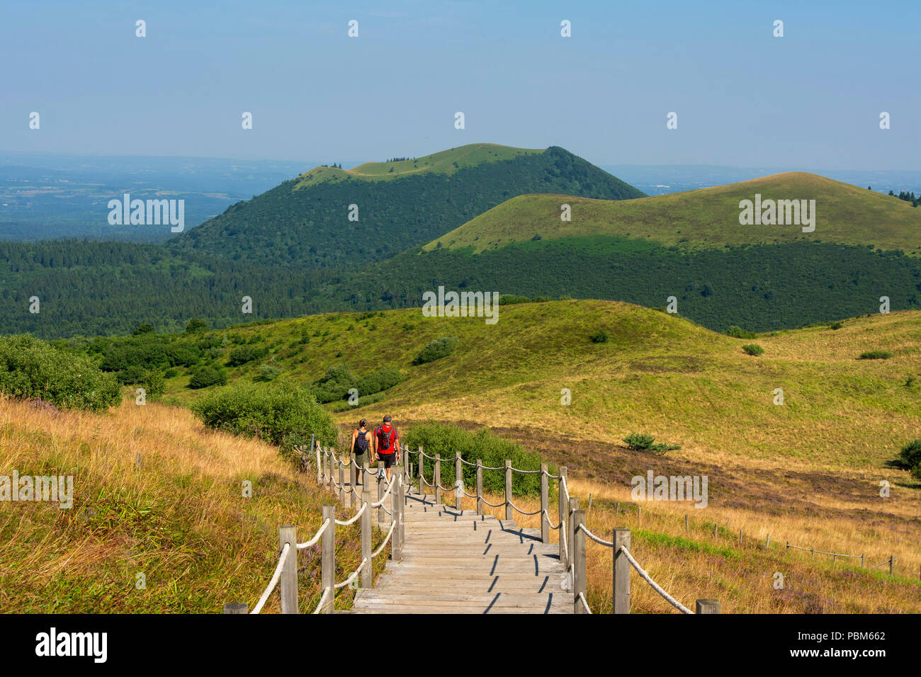 Hikers walking in regional natural park of Auvergne Volcanoes, Unesco World heritage, Puy de Dome depatment, Auvergne-Rhone-Alpes, France - Stock Image