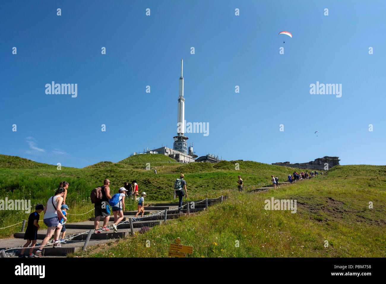 Tourists near TV transmitter of Puy de Dome, Regional natural park of Auvergne Volcanoes, Unesco World heritage, Puy de Dome depatment, Auvergne-Rhone - Stock Image