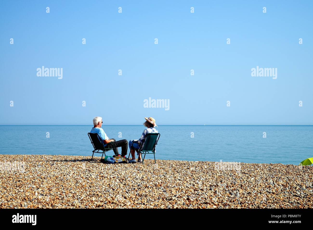Elderly white couple sitting on the beach at Hastings on a hot summers day, East Sussex England UK Stock Photo