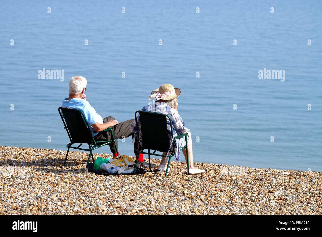 Elderly white couple sitting on the beach at Hastings on a hot summers day, East Sussex England UK - Stock Image