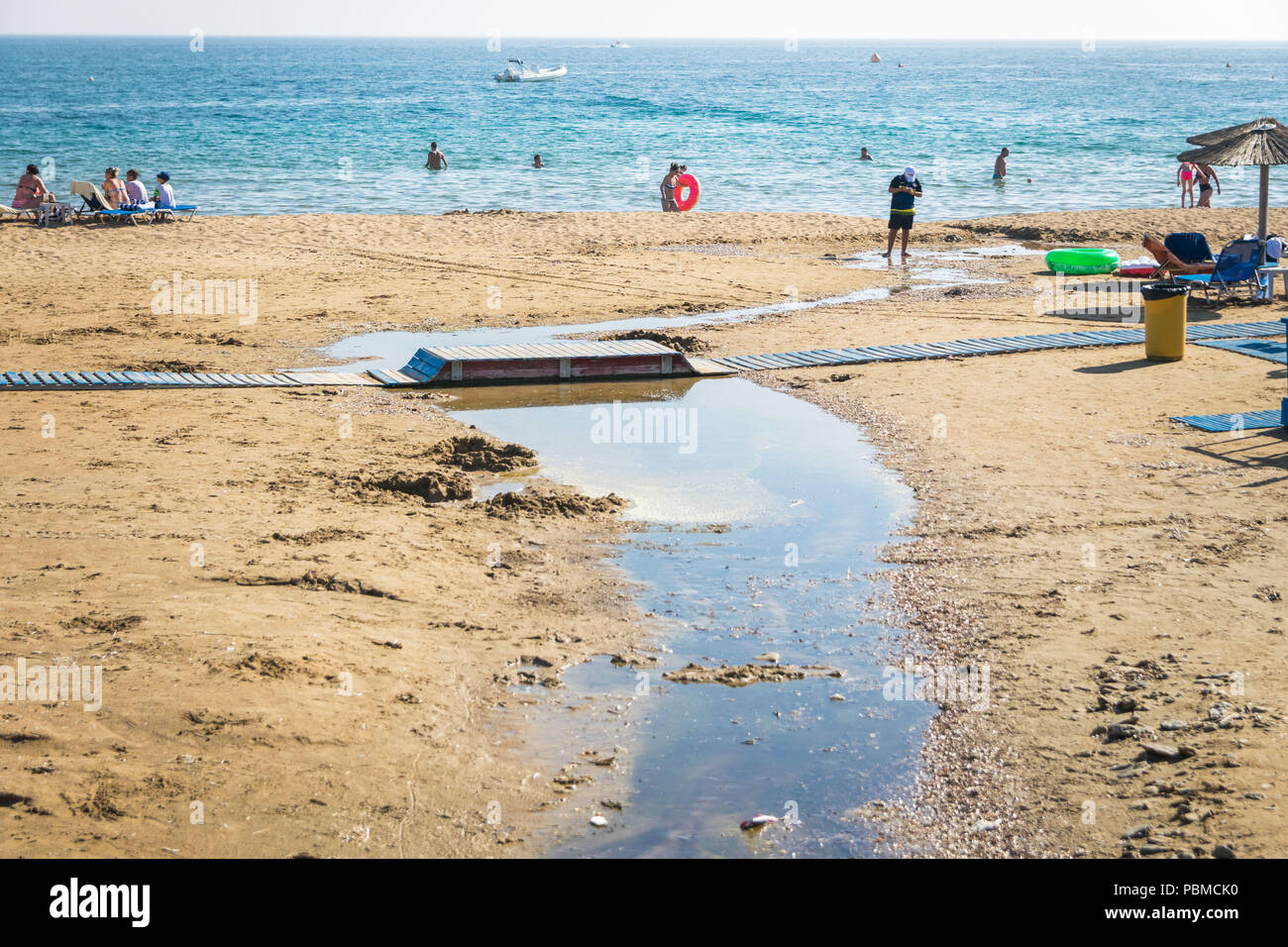 Waste water or raw sewage go directly into sea, ocean. While tourists is on the beach. Dirty beach. - Stock Image