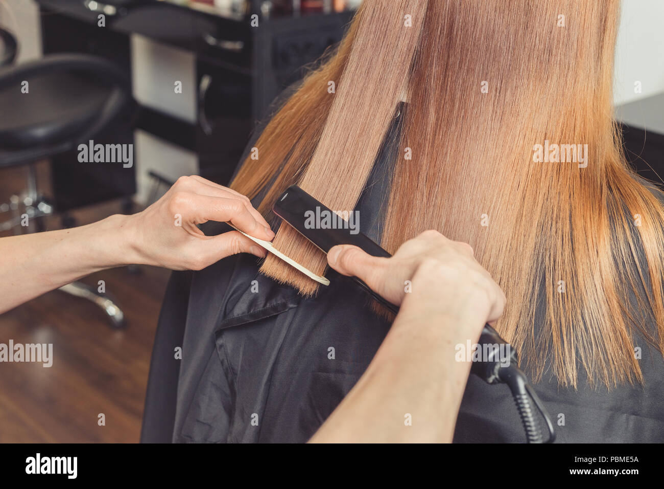 Hair straightening at beauty salon. Hairdresser making a hairstyle for client with a hair iron - Stock Image