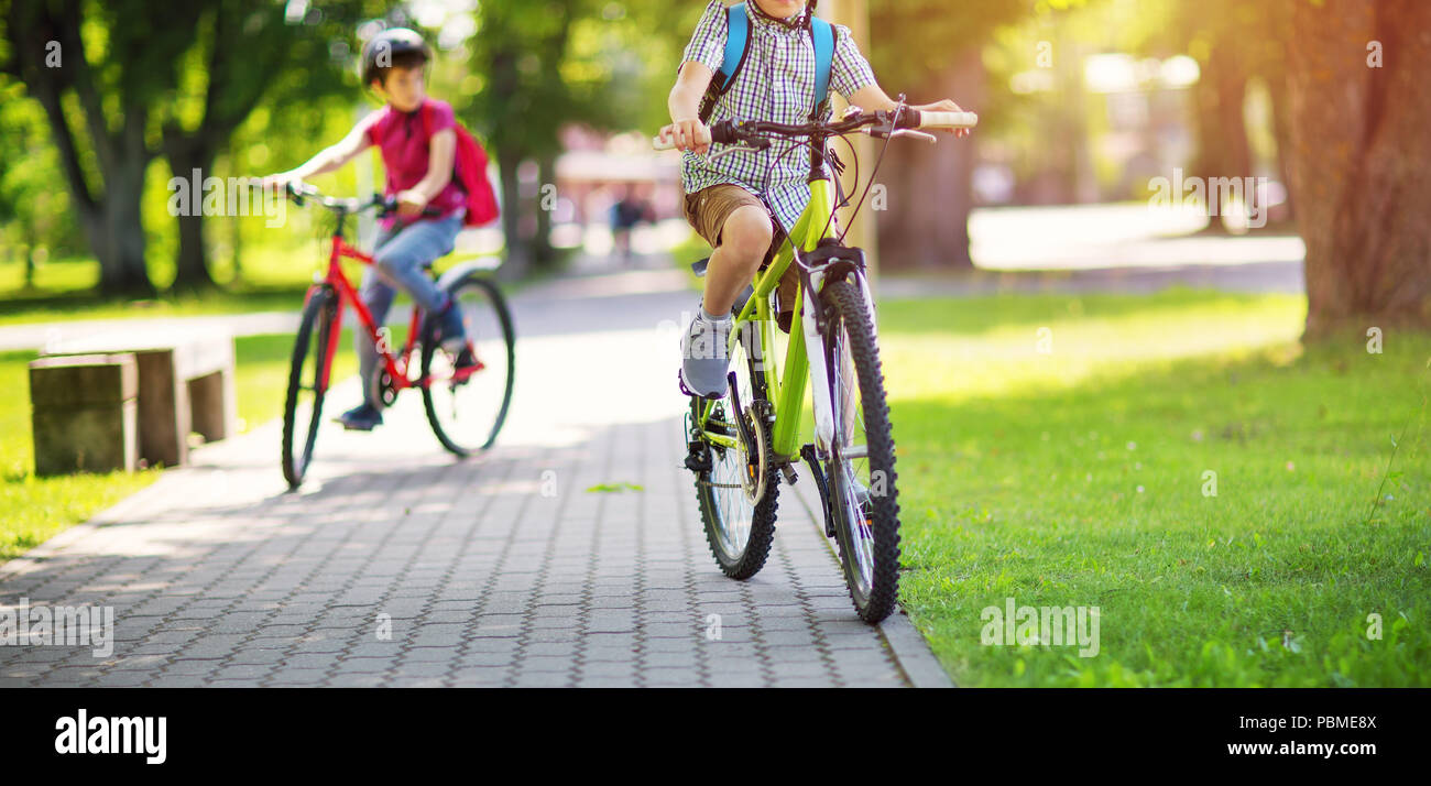 Children with rucksacks riding on bikes in the park near school - Stock Image
