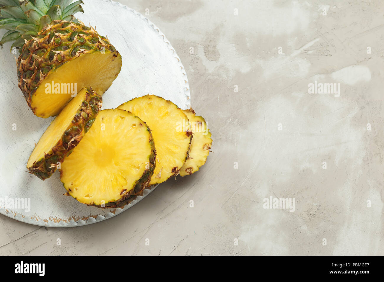 Fresh sliced pineapple on a white wooden cutting board. Concrete table backround. Top view, space for your text - Stock Image