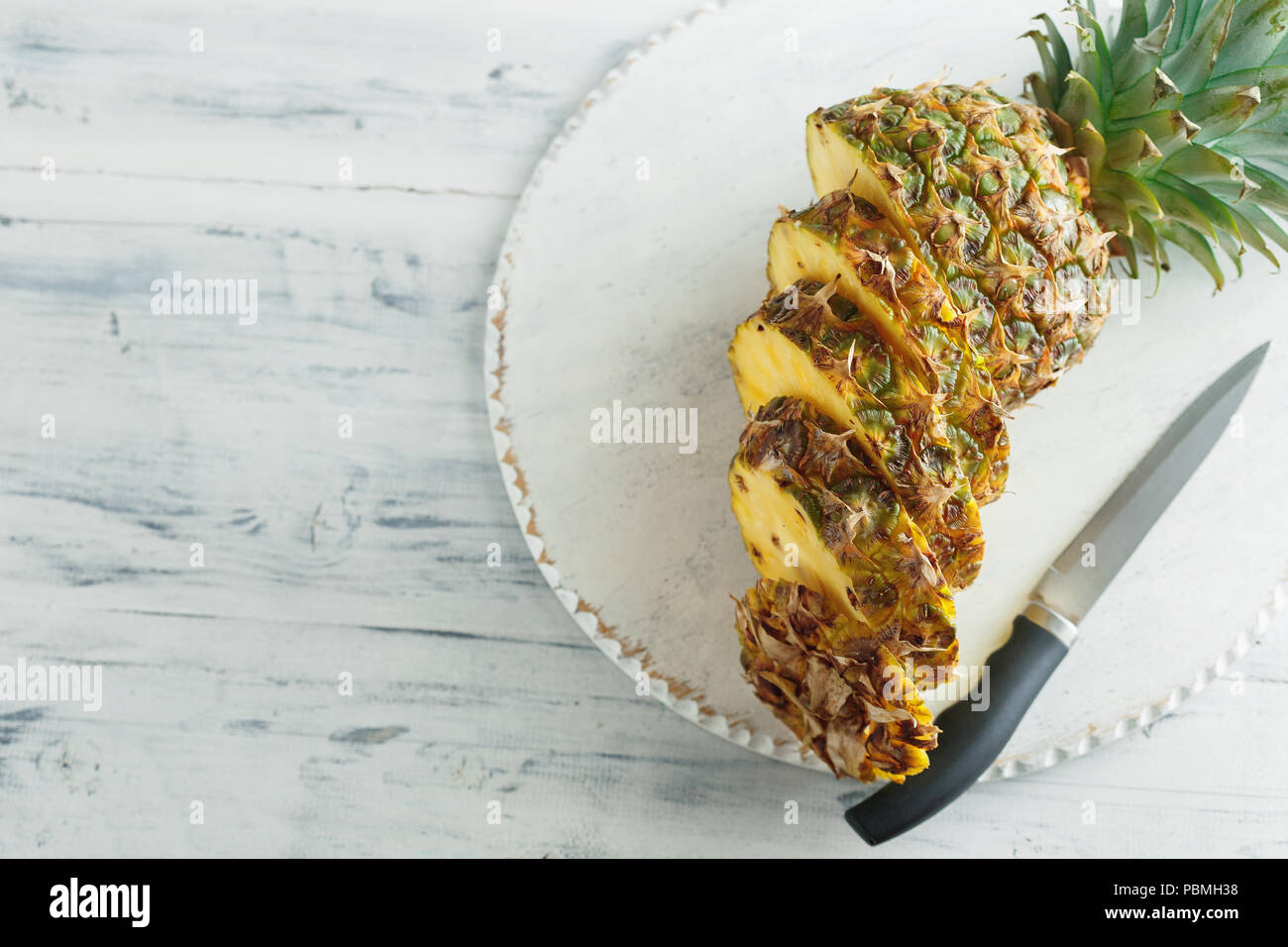 Fresh sliced pineapple on a white wooden cutting board. Top view - Stock Image