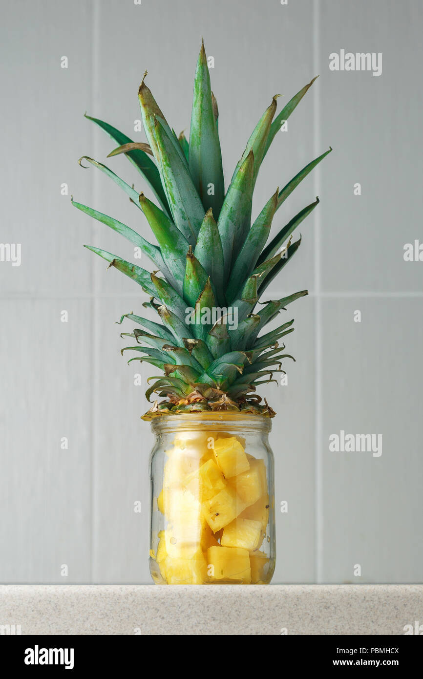 Fresh juicy pineapple pieces in a glass jar on the kitchen table against grey tile background - Stock Image