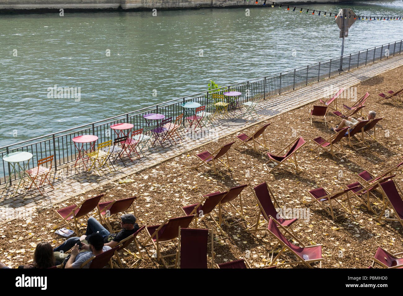People enjoying the summer afternoon on the Seine River right bank, part of the Paris Plages event. France. - Stock Image