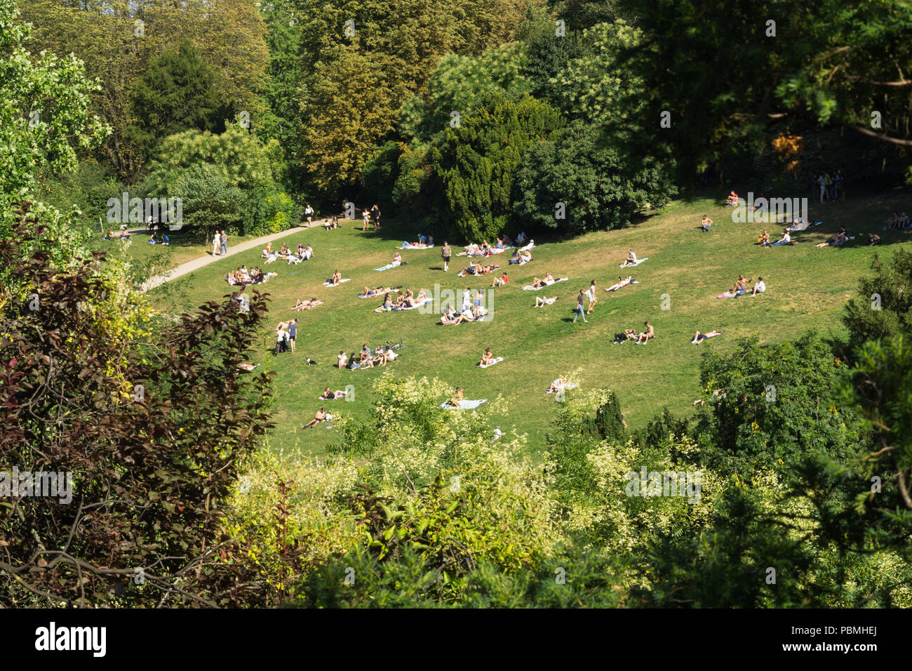 Paris park - Top view of people enjoying hot summer afternoon on the slope of Parc des Buttes Chaumont in Paris, France. - Stock Image