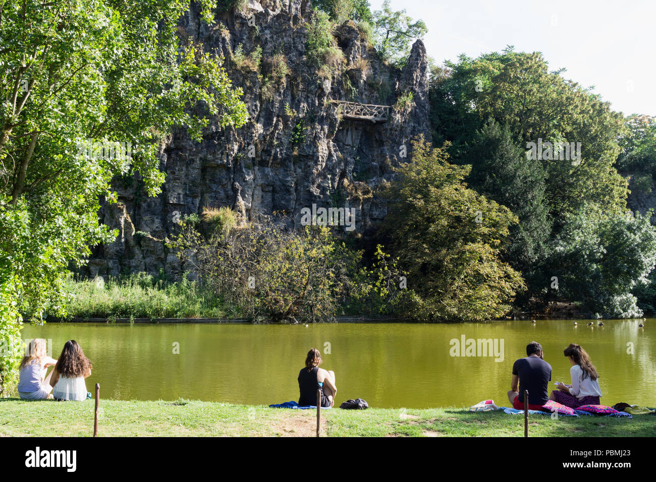 Paris park with lake - People relaxing near the lake at the Park des Buttes Chaumont in Paris, France, Europe. - Stock Image