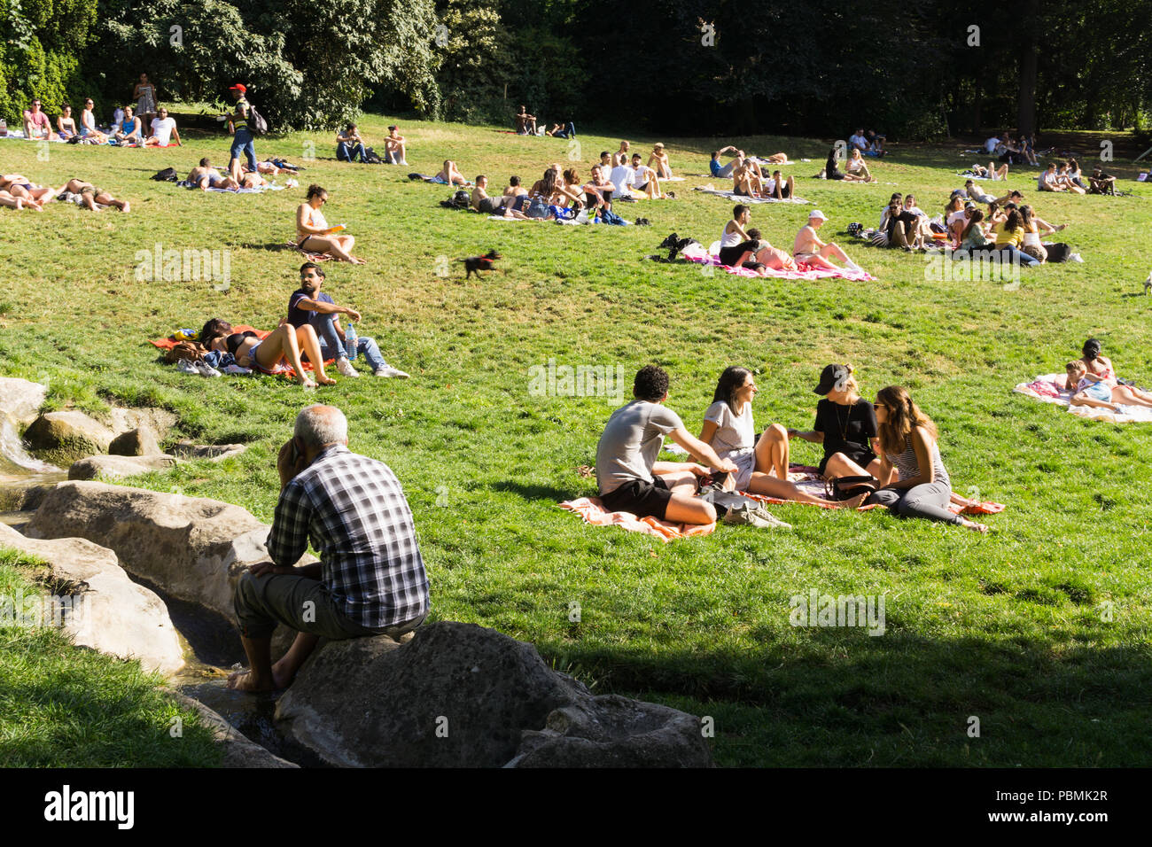 Paris park - People enjoying hot summer afternoon in the Parc des Buttes Chaumont in Paris, France, Europe. Stock Photo