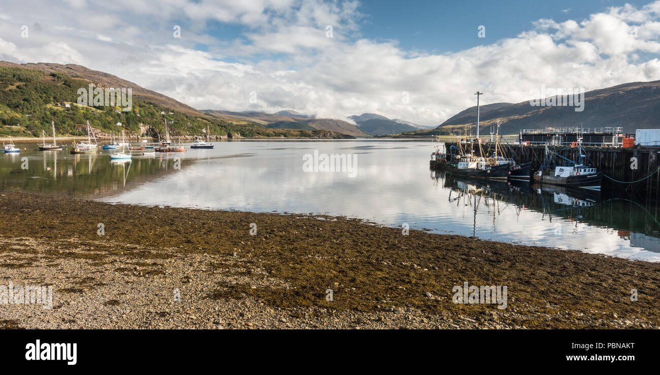 Fishing boats are moored in Loch Broom at Ullapool, under the mountains of the Northwest Highlands of Scotland. - Stock Image