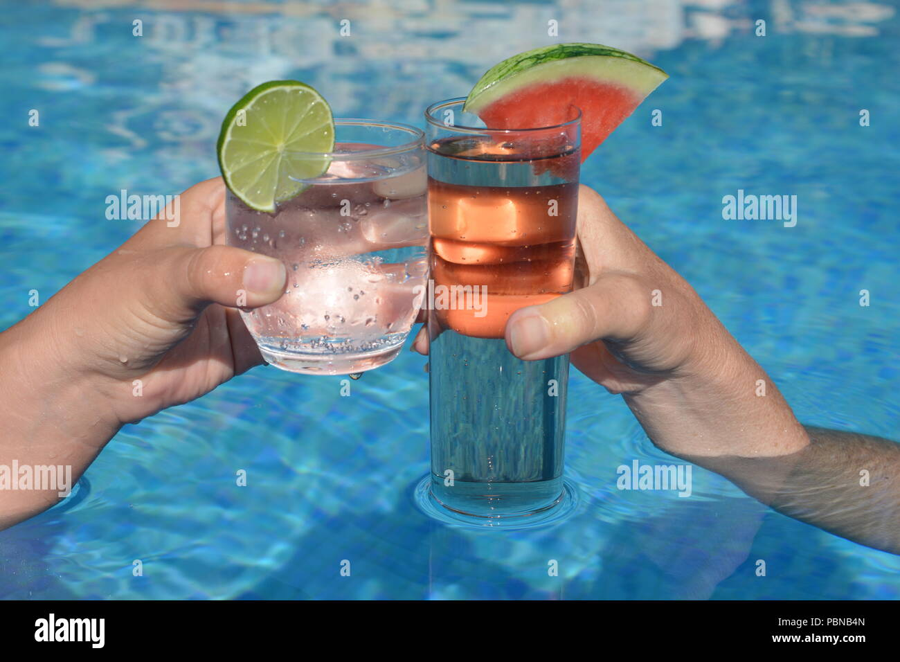 Cheers!  Enjoying a refreshing cocktail in the swimming pool - Stock Image