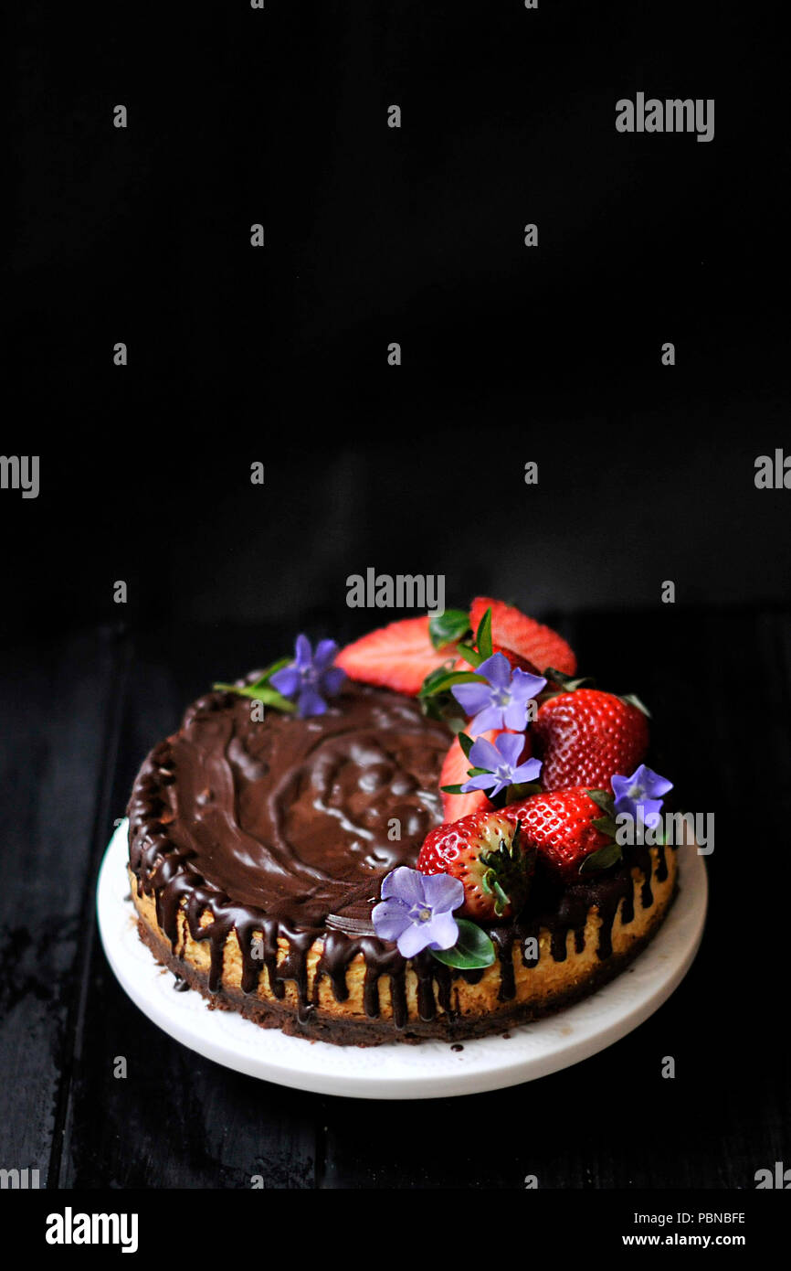 chocolate cake with berries on a black background. sweet homemade pastries - Stock Image