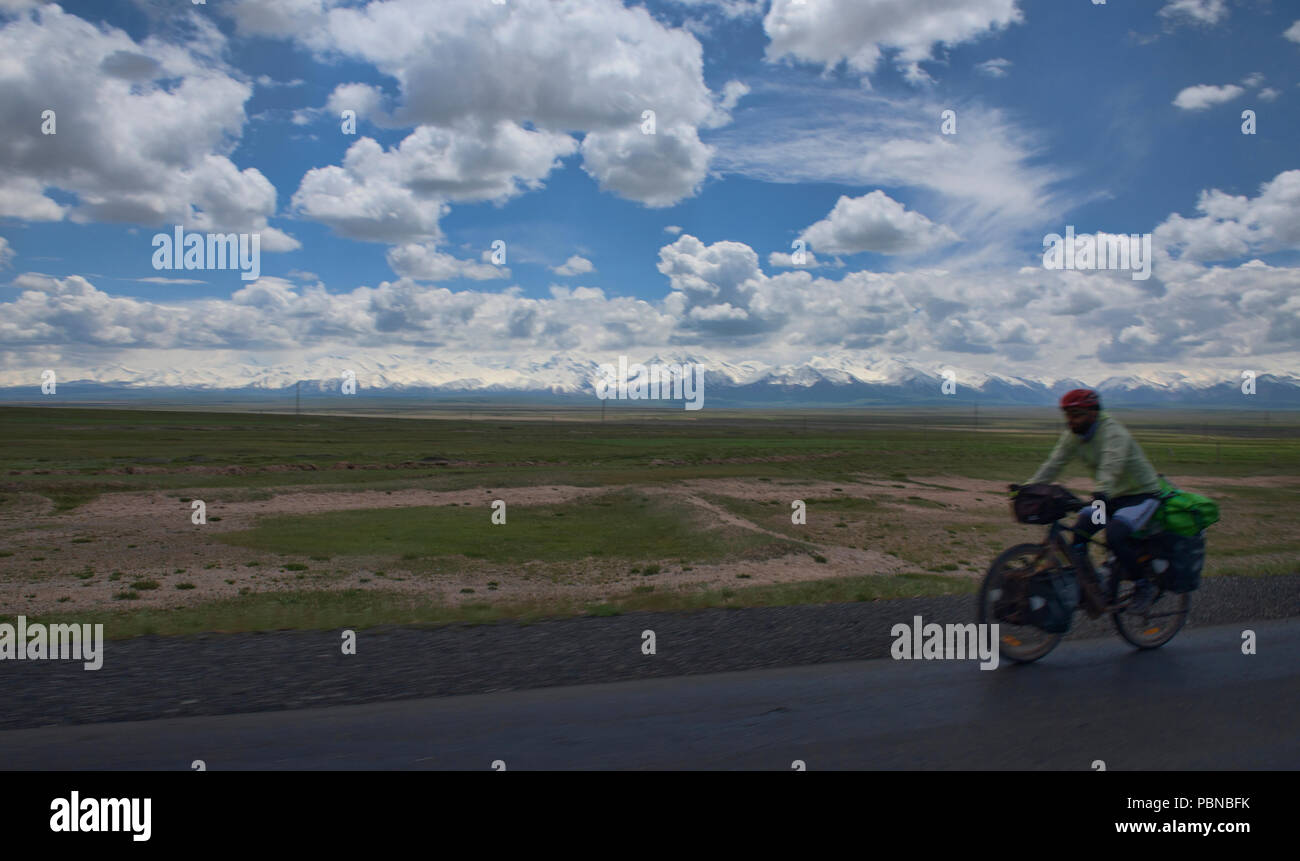 Cyclist in motion in front of the high Pamirs at the start of the Pamir Highway, Sary Tash, Kyrgyzstan Stock Photo