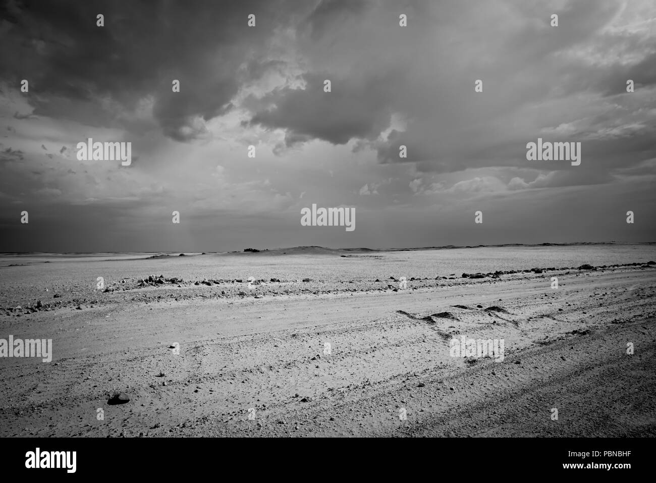 Dusty bumpy road through desert of Namibia as storm clouds collect overhead creating contrasting sky patterns - Stock Image