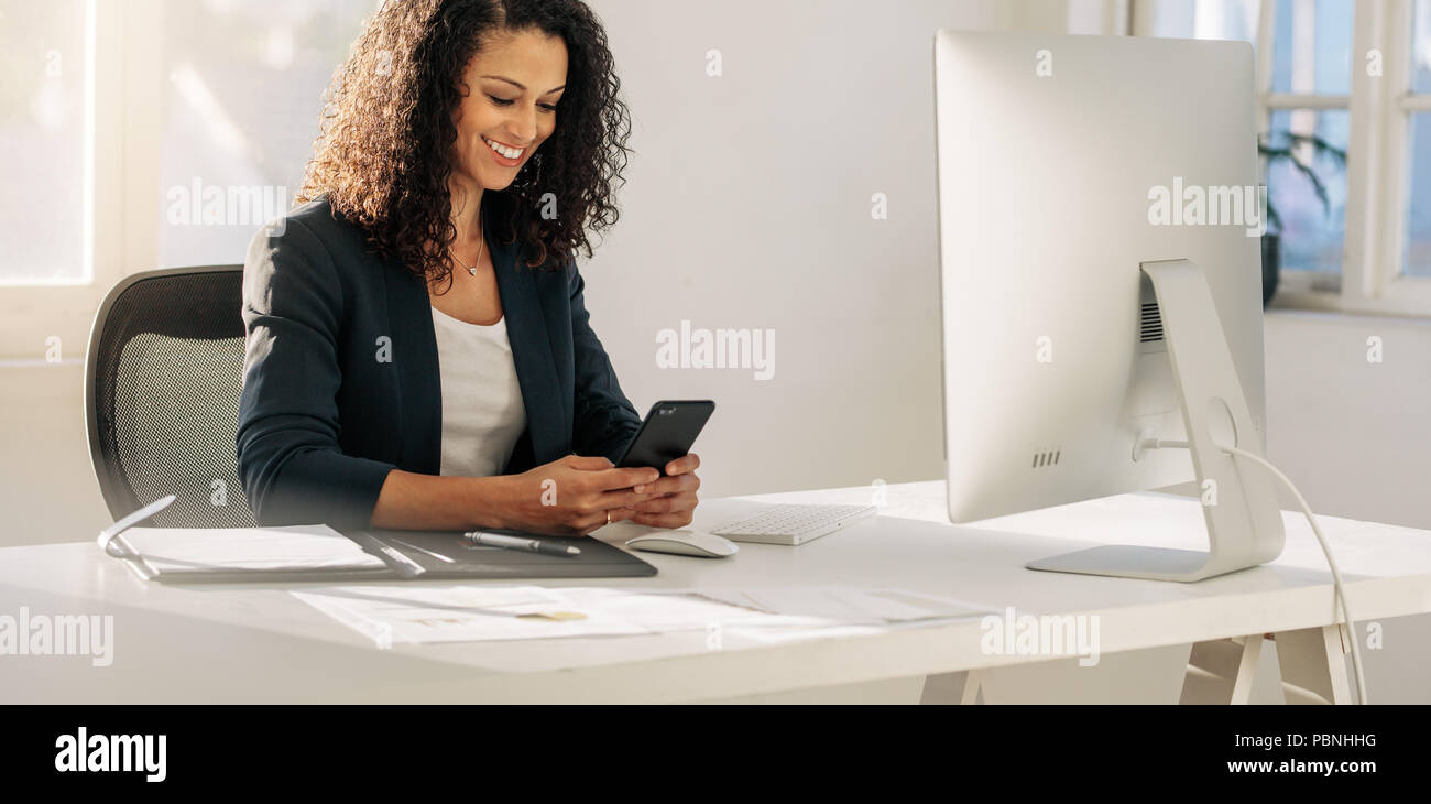 Smiling woman entrepreneur at her desk in office checking her mobile phone. Woman sitting in front of computer looking at cell phone. - Stock Image
