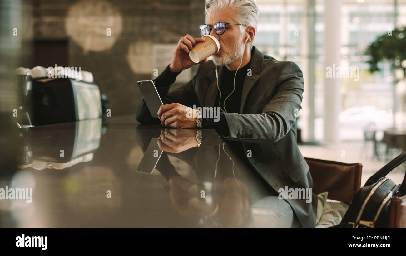 Mid adult businessman sitting at a cafe drinking coffee and using smart phone. Caucasian man in earphones looking at his cellphone in coffee shop. - Stock Image