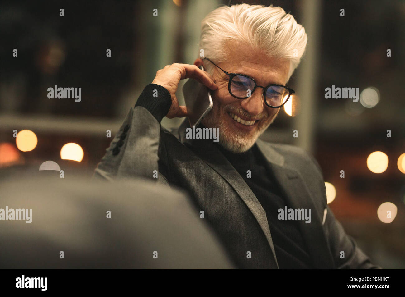 Mature business executive making a phone call and smiling. Caucasian man with eyeglasses talking on mobile phone in office. - Stock Image