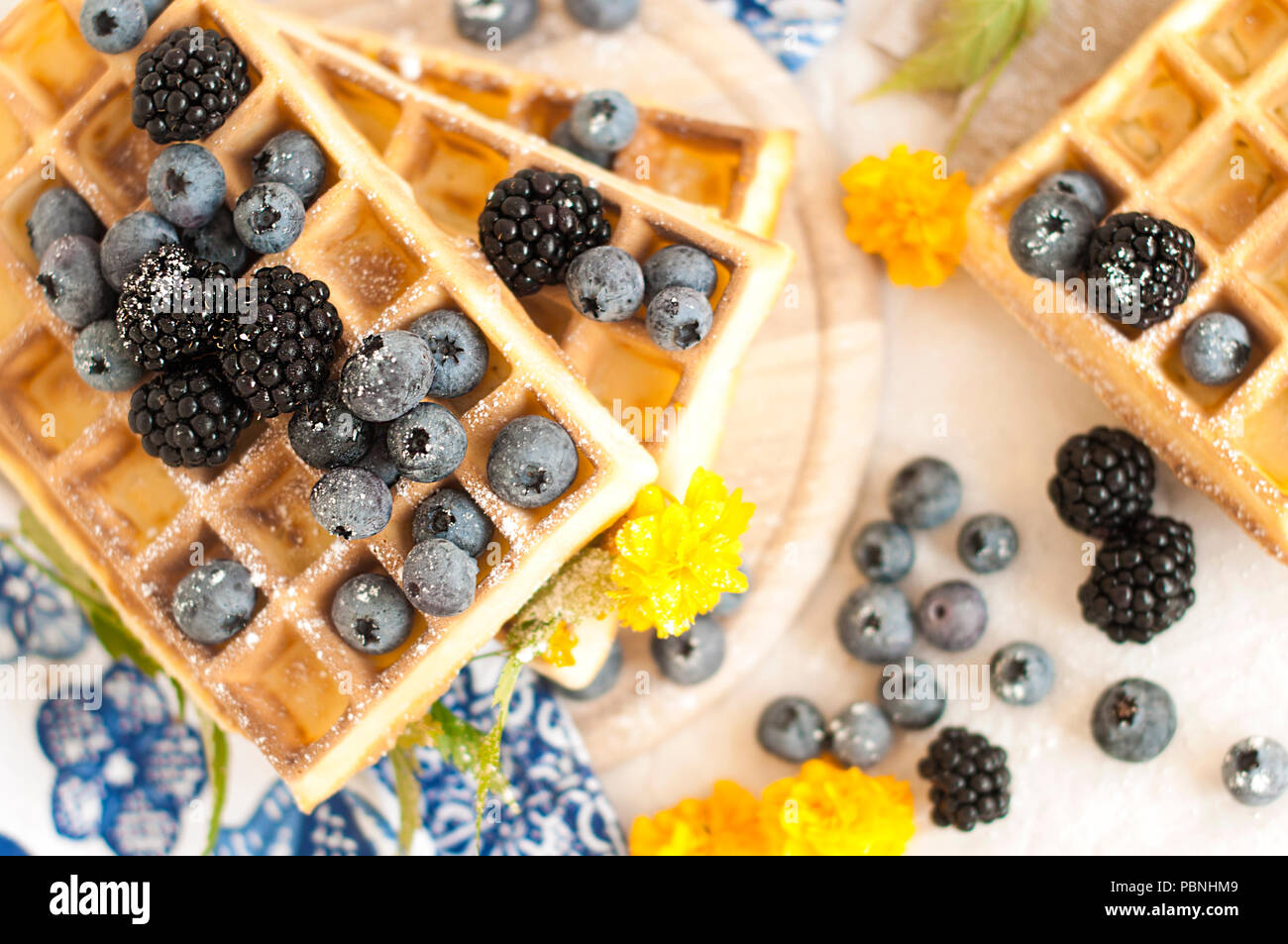 Belgian waffles with strawberries, blueberries and syrup, homemade healthy breakfast, toned image, selective focus, - Stock Image