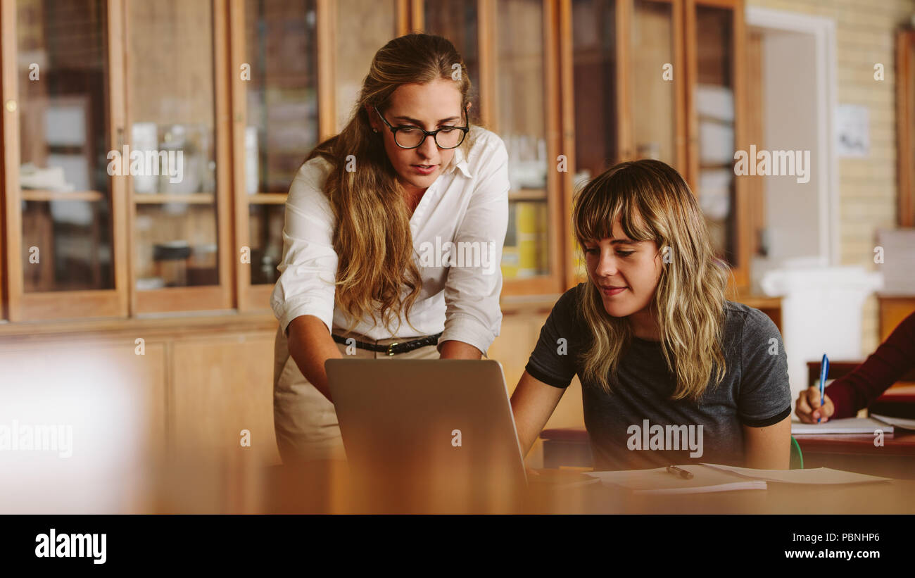 Female professor helping one of students at lecture. Teacher assisting the problem of a student in her classroom. - Stock Image