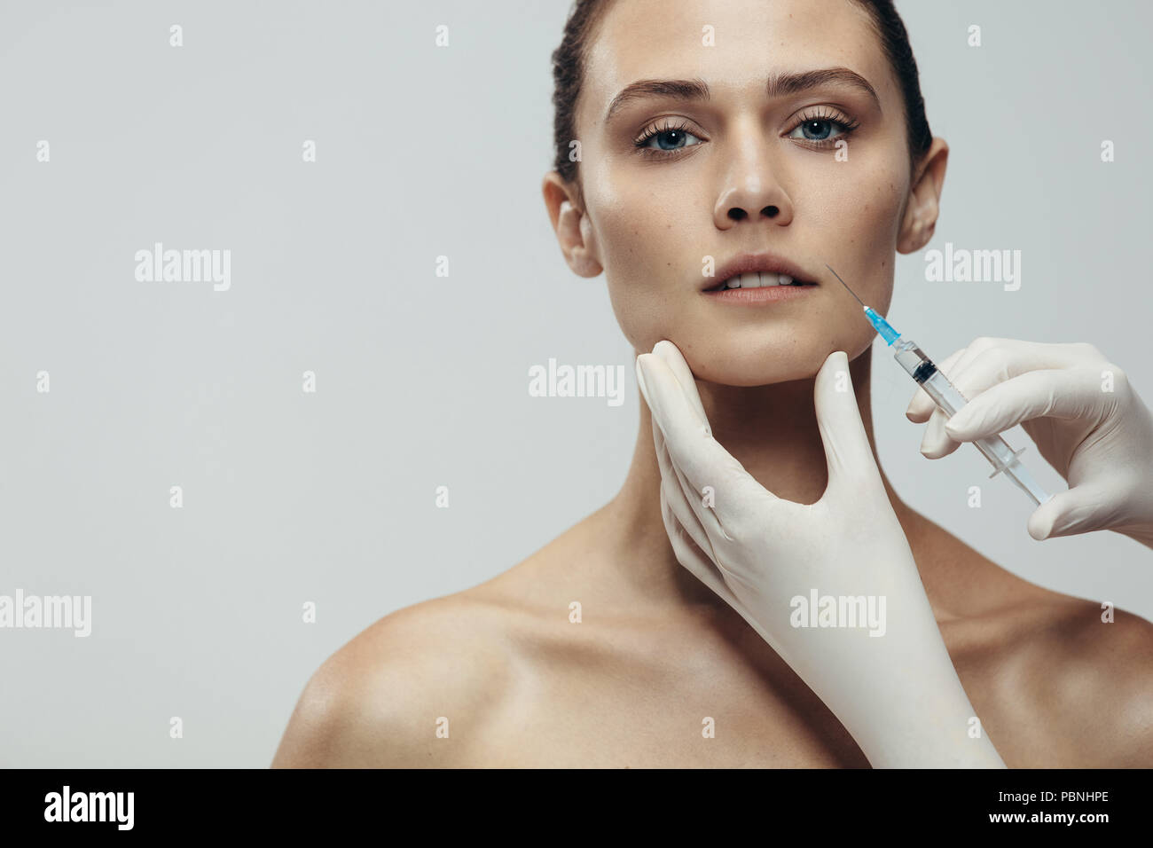Portrait of young woman getting cosmetic injection. Close up of beautiful woman gets injection in her face against grey background with copy space. - Stock Image