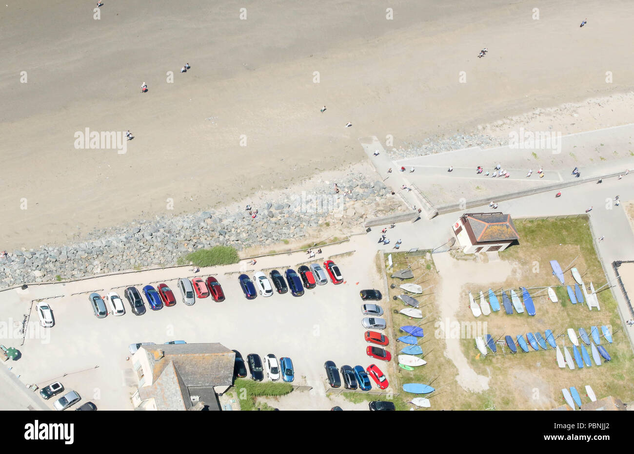 Car parked and small boats stored on beach front in Cornwall.  Birds eye view. - Stock Image