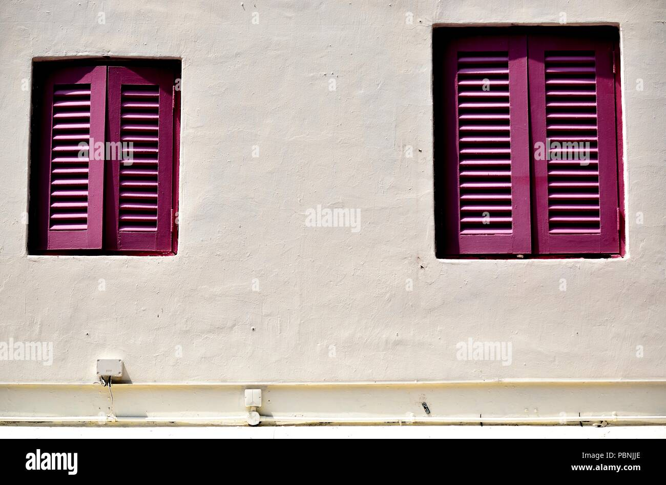 Front view of vintage wooden shuttered windows on the weathered exterior of an old Singapore shophouse in historic Kampong Glam with space for copy - Stock Image