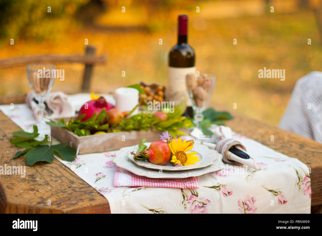 Romantic dinner in the autumn garden, table setting for a nice dinner. Wine, fruit, pomegranate and flowers. Picnic in the open air. - Stock Image