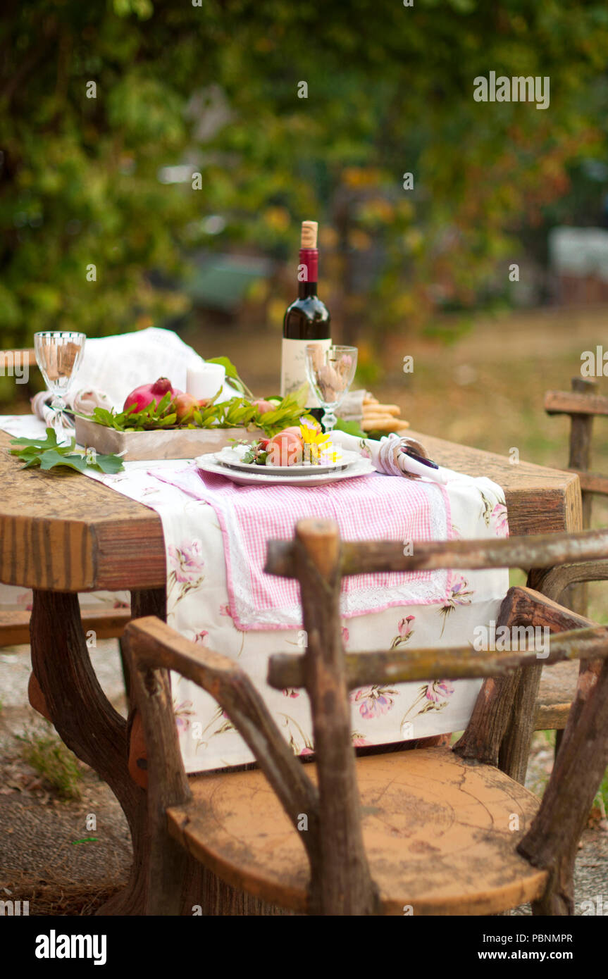 Lunch is romantic in autumn garden, atmosphere of holiday and coziness. Autumnal dinner in the open air with wine and fruit. Decor table with flowers and pomegranate. Vintage photo. - Stock Image