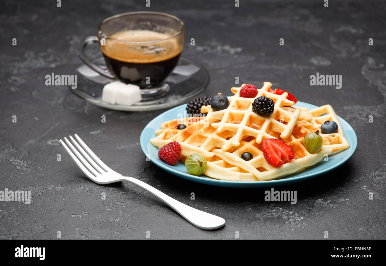 Photo of cup of black coffee with sugar with Viennese waffles with strawberries, raspberries, gooseberries and fork - Stock Image