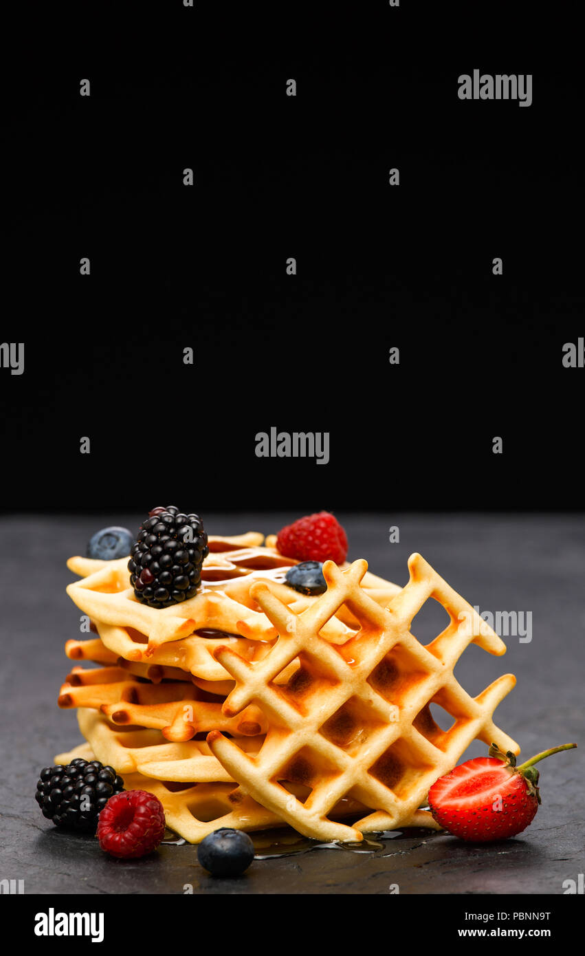 Photo of viennese wafers with berries on black background - Stock Image
