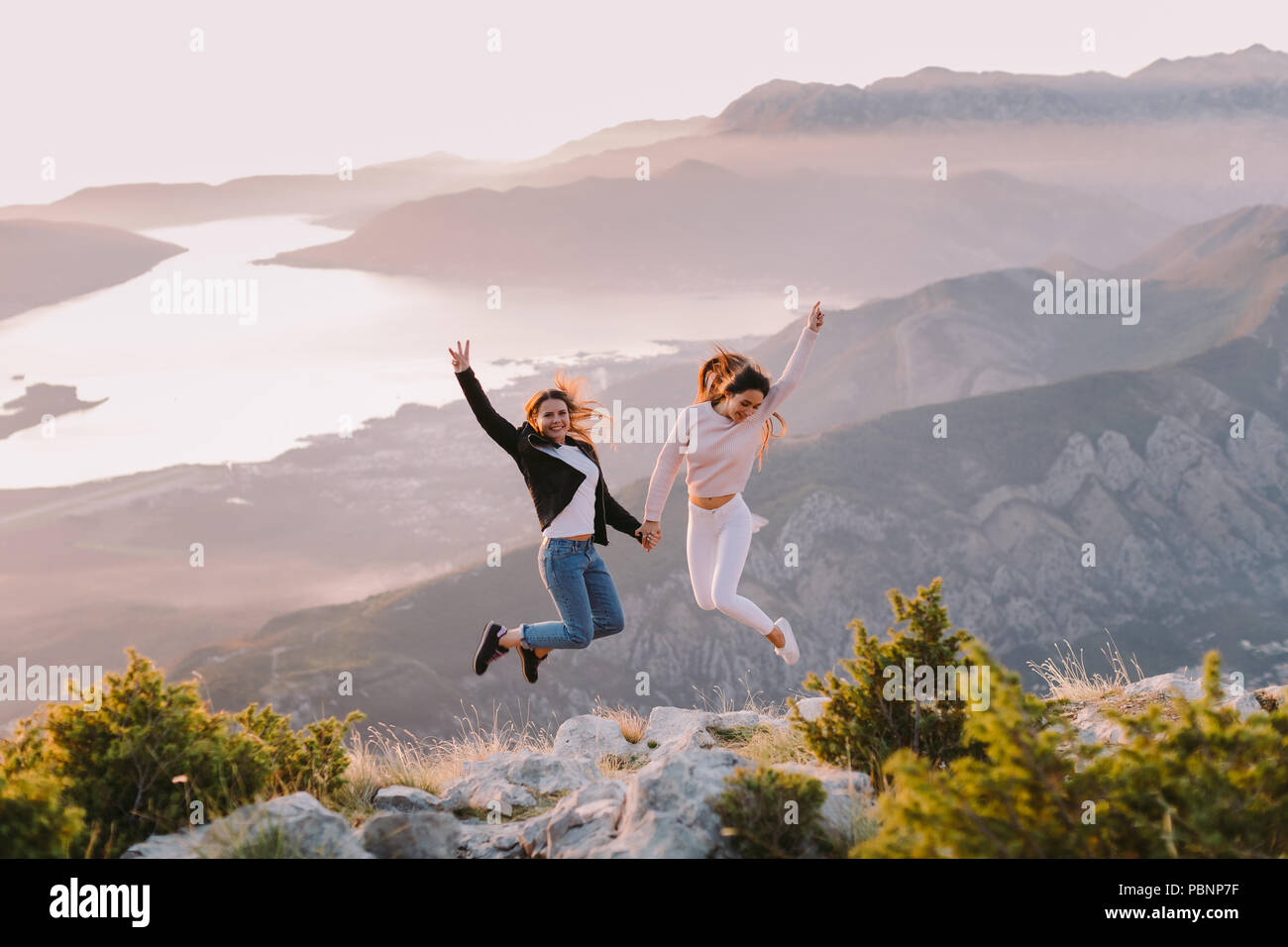 two girls travel in mountains at sunset with beautiful view. Picturesque  landscape background. - 66a458bf360bd