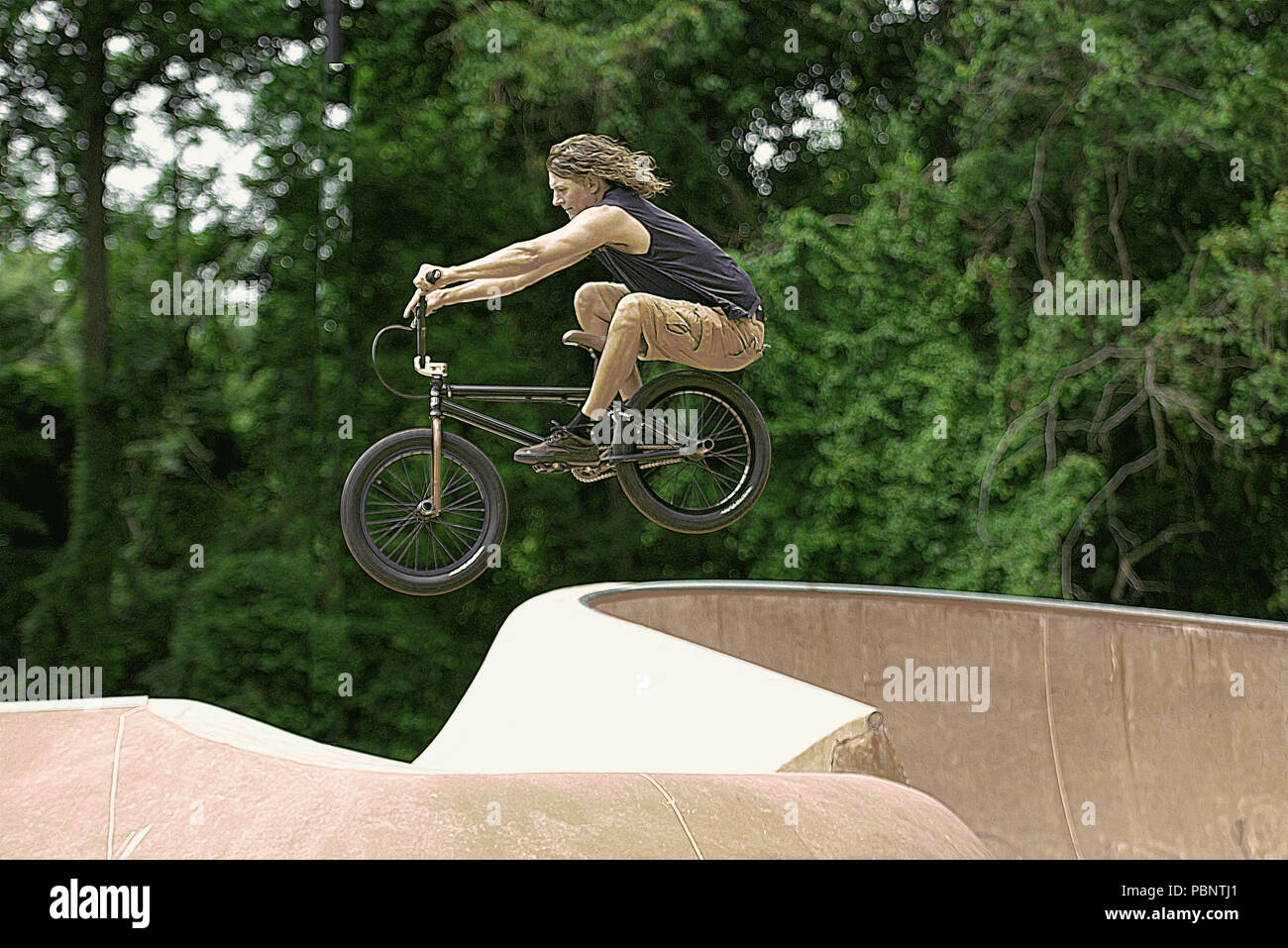 Middle age adult performing bike tricks at BMX bike and Skateboard park Stock Photo