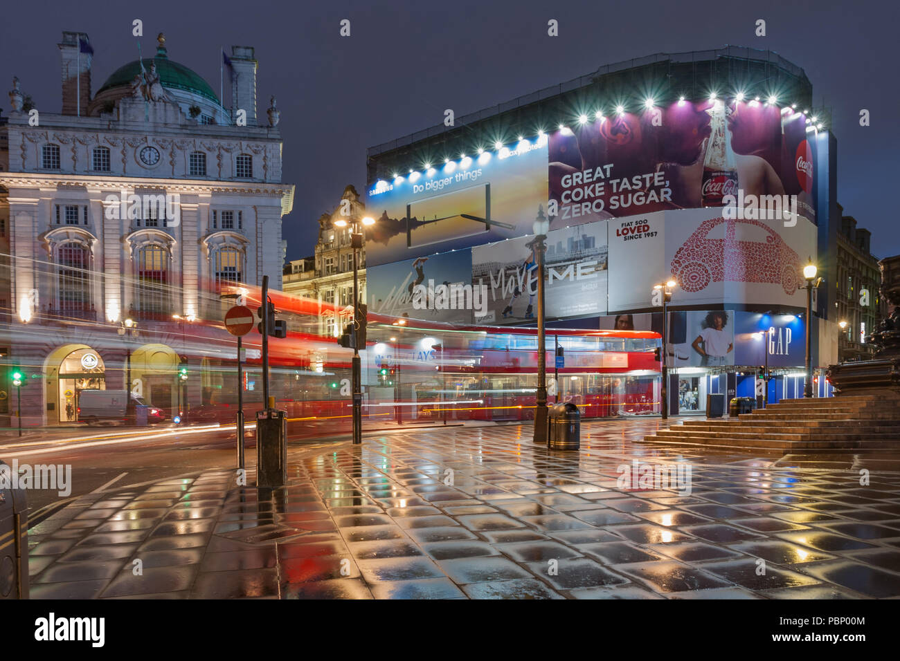 Piccadilly Circus, London-September 8,2017: Light trails from London bus on Piccadilly Circus in rainy early morning time on September 8, 2017 in Lond - Stock Image