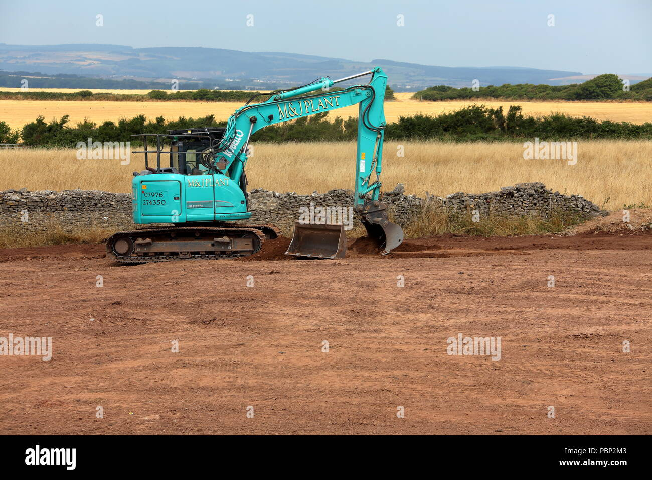 A newly commisioned large tracked digger levelling off the earth in a newly restored field before being returned to the farmer. - Stock Image