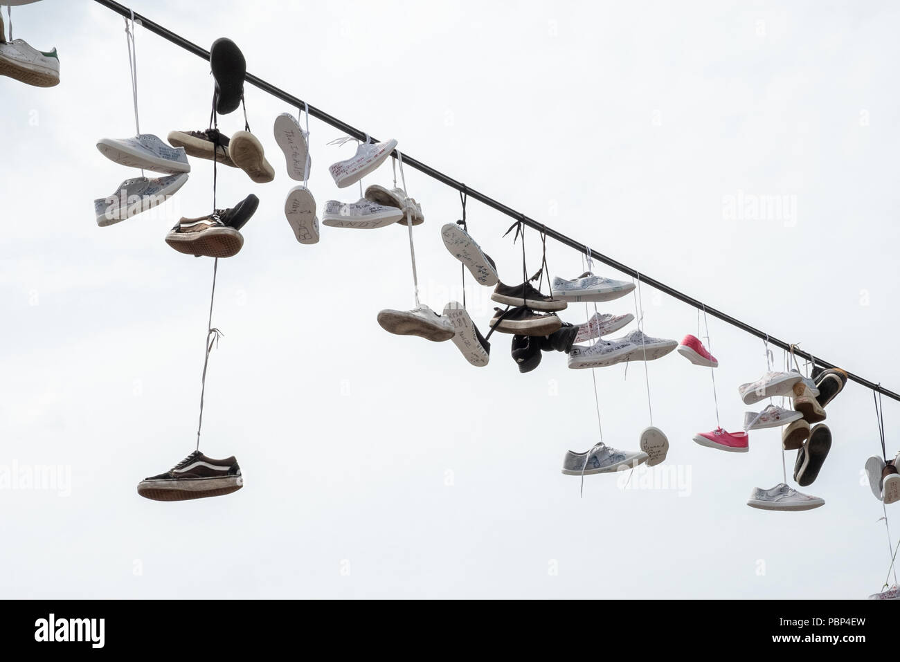 Line of pairs of shoes hanging on a line adjacent to the metronome in Prague - Stock Image