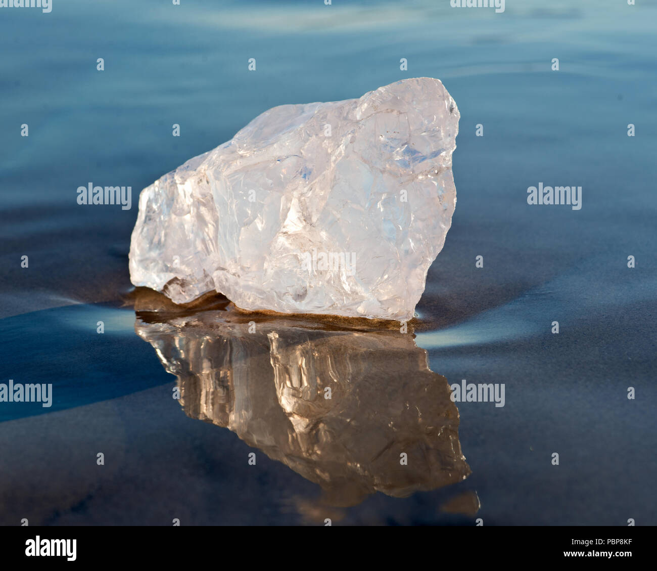 Gem grade rough Rose Quartz chunk from Madagascar lying on wet sand