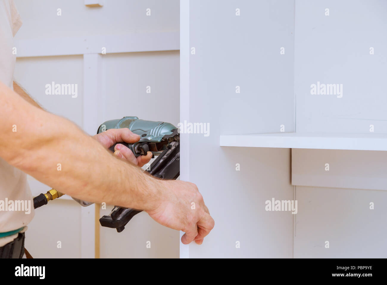 Man Assembling The Closet With Wooden Shelves Wall