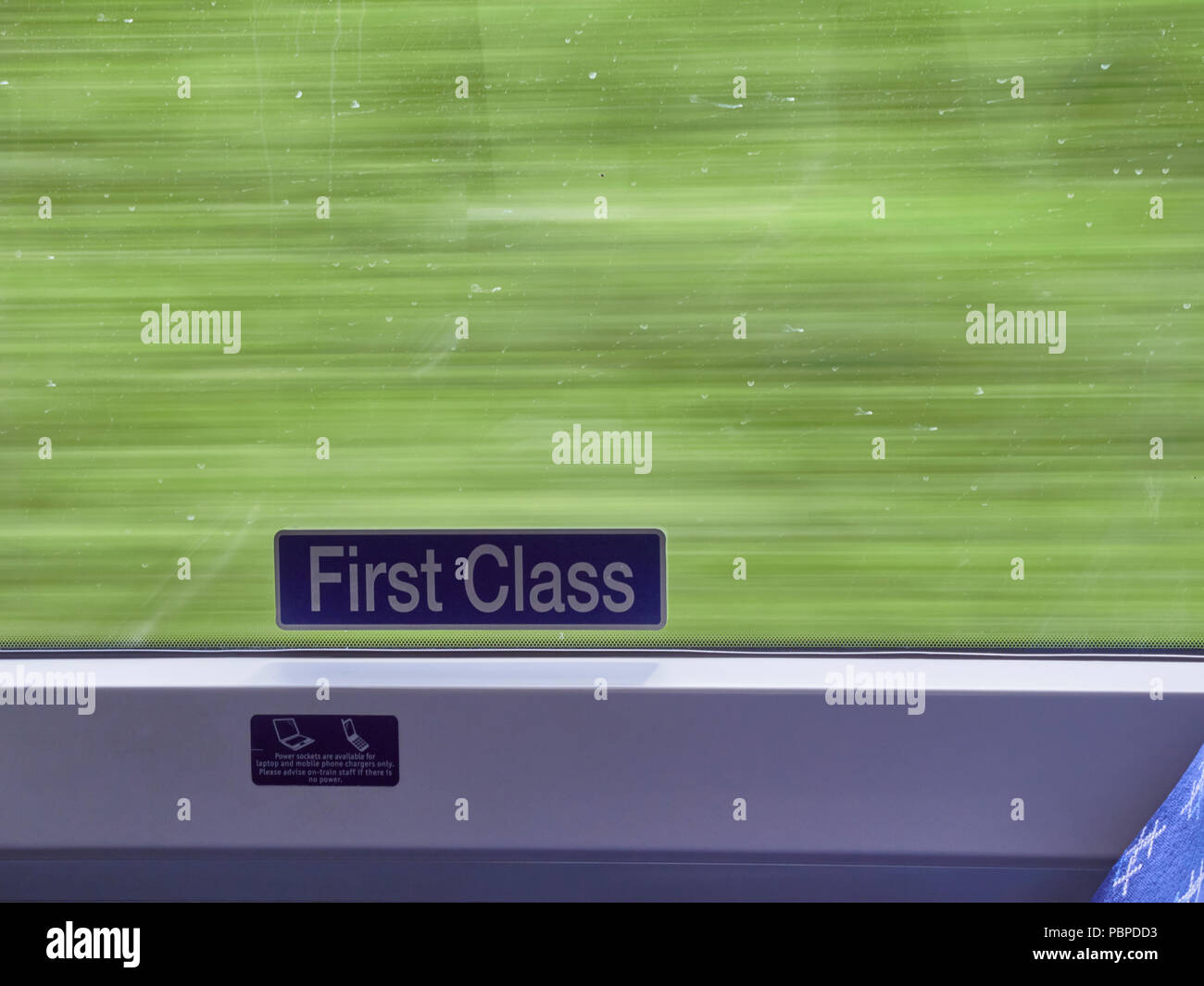 The First Class Carriage sign on a Moving Train with a blurred green background showing the speed of travel. North East Scotland, UK. - Stock Image