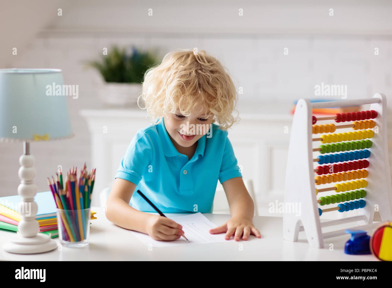 Child doing homework at home. Little boy with wooden colorful abacus ...