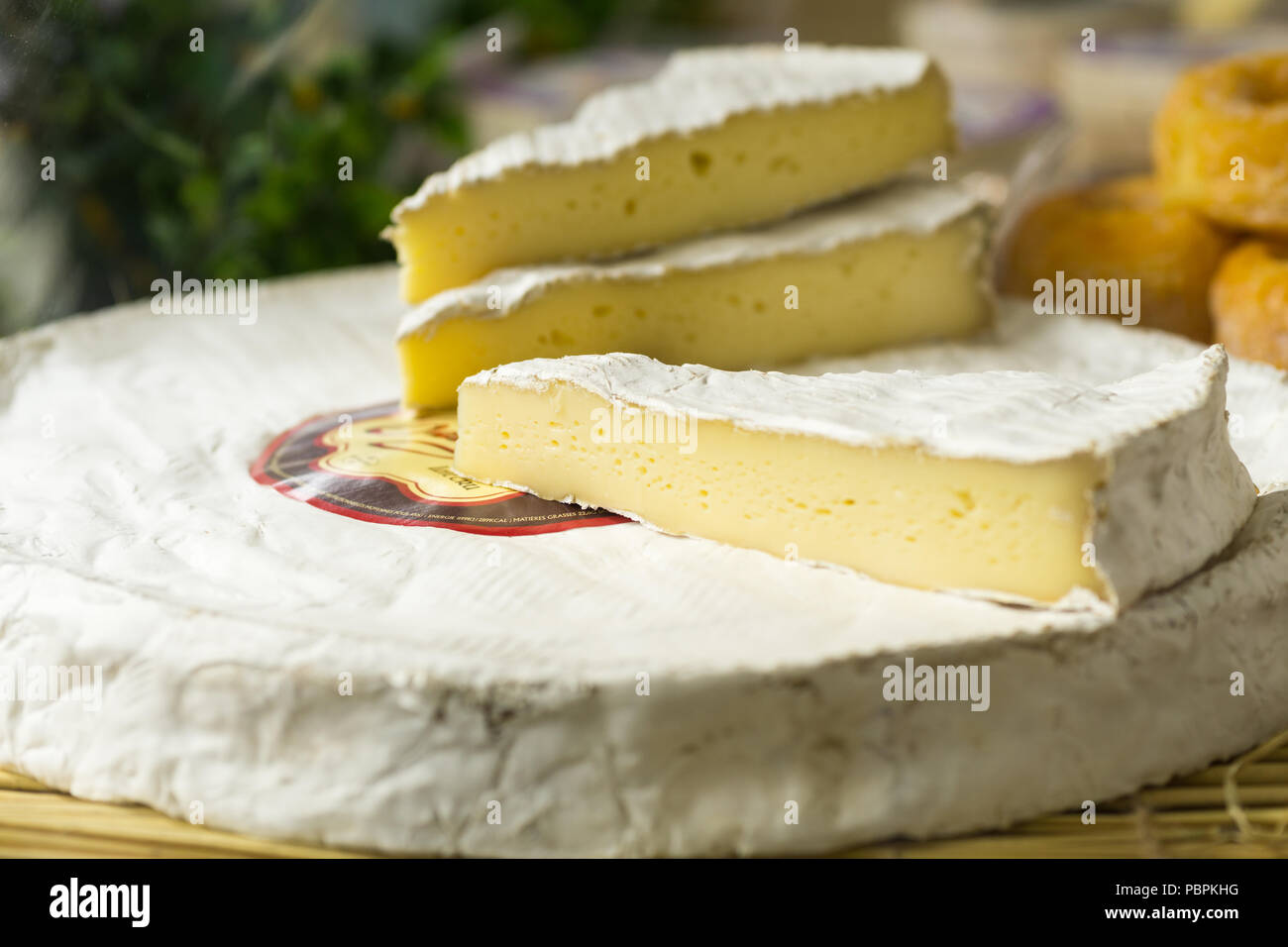 Close up of cut brie cheese sold on a Paris market, France. - Stock Image
