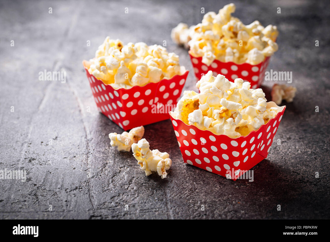 Popcorn in red polka dot pack on black concrete table. Selective focus - Stock Image