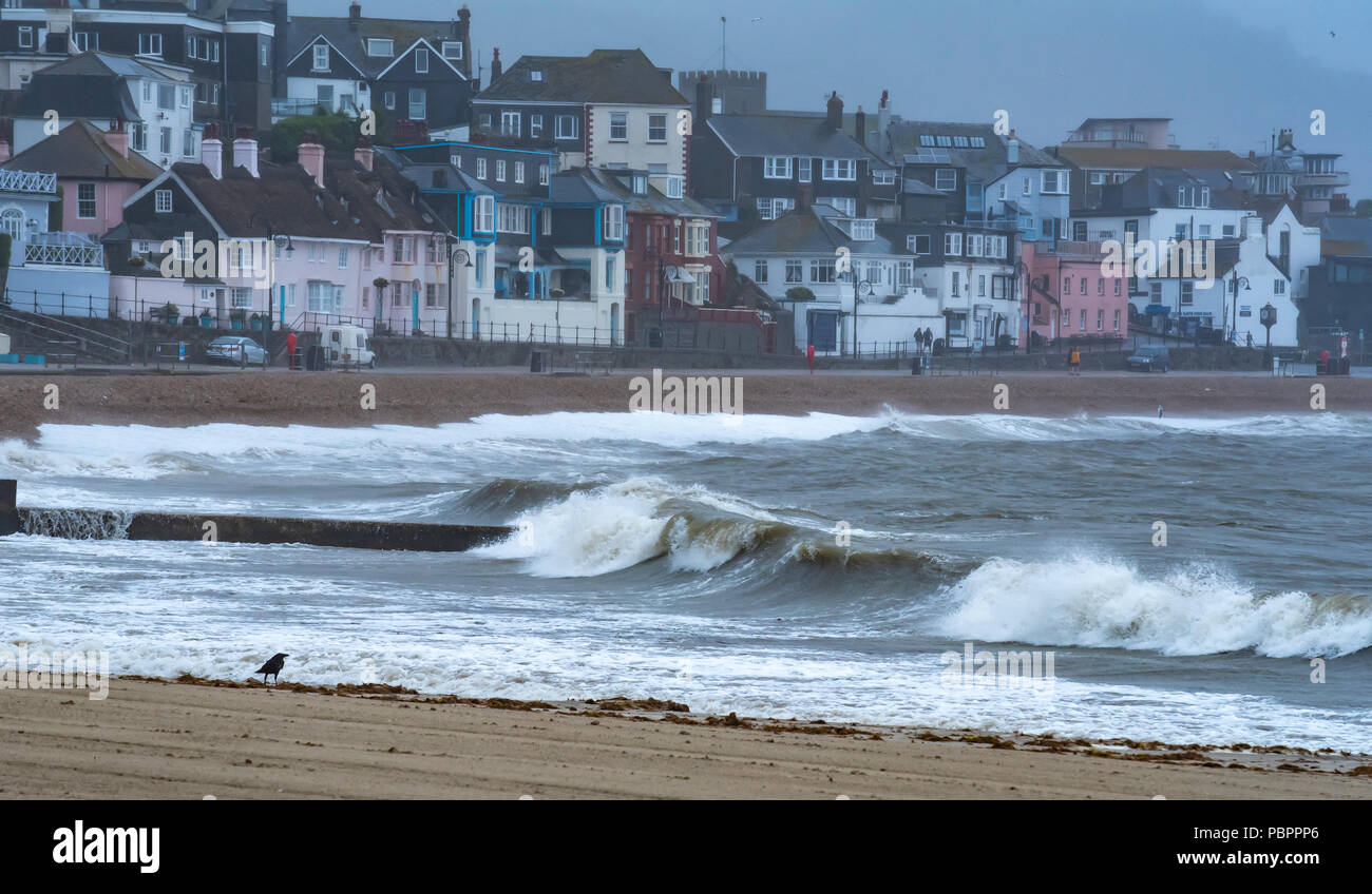 Lyme Regis, Dorset, UK. 29th July 2018.  UK Weather: Storm waves crash into seafront at Lyme Regis. A wild storm hits the seafront and the historic Cobb Harbour at the seaside resort of Lyme Regis bringing a temporary lull to the record breaking summer heatwave. Credit: Celia McMahon/Alamy Live News - Stock Image